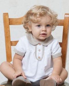 Bebé rubio vestido con ranita de bautizo de lino blanca con detalles de lino rústico