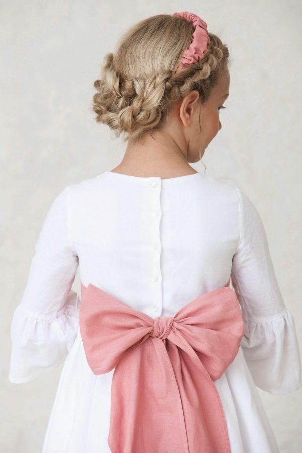 vestido de comunión de niña con volantes en las mangas y el bajo de la falda con fajín rosa