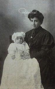 origen de los faldones de bautismo. Imagen del siglo xixi de una mujer vestida de negro con un niño vestido de Bautizo con capota