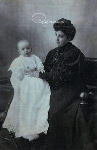 origen de los faldones de bautismo. Imagen del siglo xixi de una mujer vestida de negro con un niño vestido de Bautizo