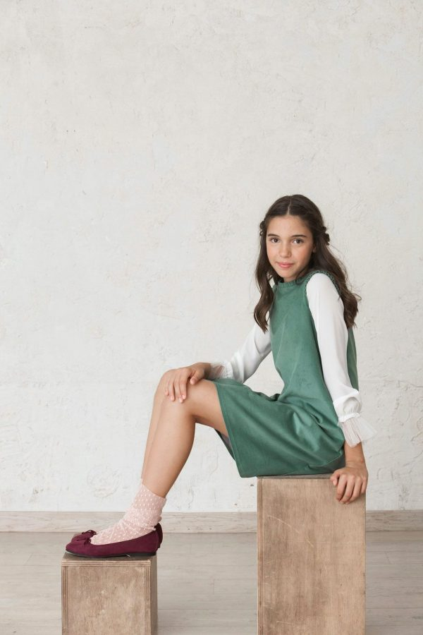 blusa blanca de manga larga de tul conjuntada con vestido pichi verde